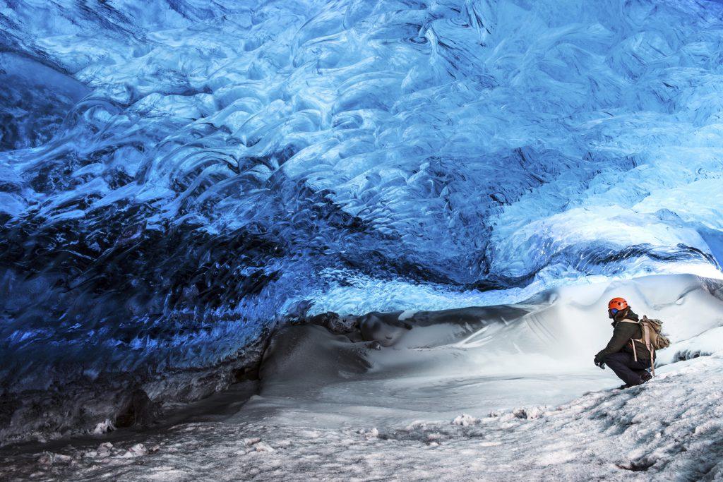 Man traveler enjoying exotic landmark, sitting in the ice cave, Skaftafell glacier, Vatnajokull National park, amazing nature of Iceland